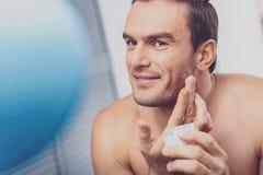 Ciemnowłosy mężczyzna bierze opiekę jego skóra zdjęcie stock