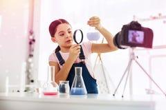 Ciemnowłosy uczennicy mienia powiększać - szklana patrzeje błękitna substancja fotografia royalty free