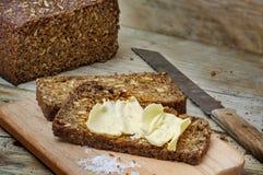 Ciemny żyto chleb z ziarnami, masłem i solą na nieociosanym drewnie, obraz royalty free