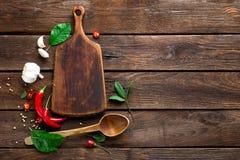 Ciemny drewniany kulinarny tło z różnorodnymi ziele i pikantność, odgórny widok, wieśniak zdjęcia stock