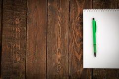 Ciemny drewno stół z notatnikiem i piórem Odgórny widok Fotografia Royalty Free