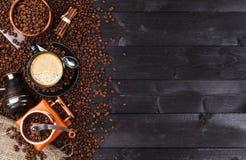 Ciemny kawowy tło, odgórny widok z kopii przestrzenią Czarna filiżanka kawy, zmielona kawa, młyn, puchar Zdjęcia Royalty Free