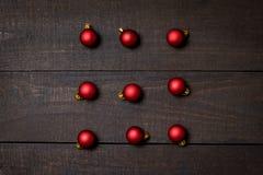 Ciemny nieociosany drewno stół flatlay - Bożenarodzeniowy tło z czerwonymi boże narodzenie ornamentami Odgórny widok z bezpłatną  obrazy stock