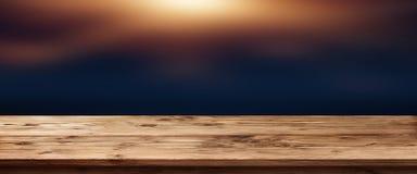 Ciemny tło z zaświecającym drewnianym stołem zdjęcie stock