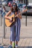 Ciemny z włosami żeński piosenkarz na ulicie z okularami przeciwsłonecznymi i Obrazy Stock