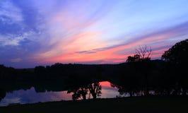 Ciemny zmierzch z ciemnopąsowymi chmurami Zmierzch nad jeziorem Półmrok nad rzeka zdjęcie royalty free
