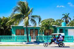 Cienfuegos. Bike taxi in typical Cienfuegos street, beautiful colours and palms Royalty Free Stock Photo