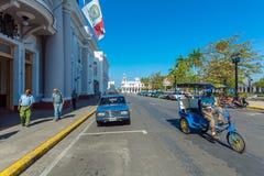 CIENFUEGOS, CUBA - MAART 30, 2012: Fietstaxis en voetgangers Royalty-vrije Stock Fotografie