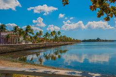 Cienfuegos Kuba: Promenera i staden, kokosnötpalmträd reflekteras i vattnet Solig dag med blå himmel och moln royaltyfri bild