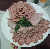 Cienki rozcięcie mięso i uwędzona kiełbasa, dekorujący z zieleniami fotografia royalty free