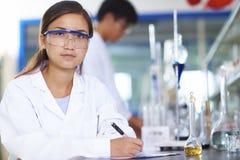 Científico asiático del laboratorio que trabaja en el laboratorio con los tubos de ensayo Imagen de archivo libre de regalías