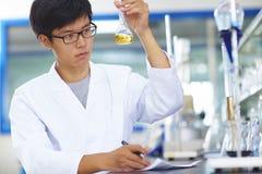 Científico asiático del laboratorio que trabaja en el laboratorio con los tubos de ensayo Foto de archivo libre de regalías