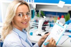 Científico atractivo joven de la mujer que investiga en el laboratorio fotografía de archivo