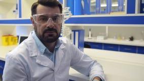 Científico barbudo que presenta para la cámara con confianza metrajes