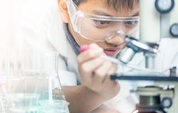 Científico con el equipo y experimentos de la ciencia, cristalería de laboratorio que contiene el líquido químico para el diseño  fotos de archivo