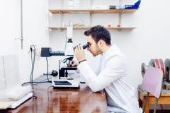 Científico con el microscopio, las muestras de examen y las puntas de prueba contaminadas en laboratorio especial fotografía de archivo libre de regalías