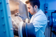 Científico con los guantes protectores del ladrón para manejar sustancias peligrosas en el ambiente estéril foto de archivo libre de regalías