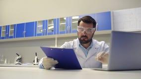 Científico concentrado que trabaja con los documentos y mecanografiar almacen de video