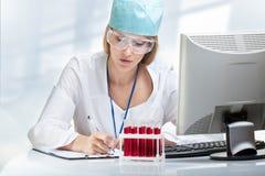 Científico de la mujer joven que examina un tubo de ensayo con el líquido rojo Foto de archivo