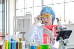 Científico de la mujer que hace el experimento y la lista de verificación foto de archivo