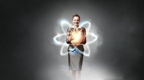 Científico de la mujer que presenta concepto de la investigación del átomo imagen de archivo