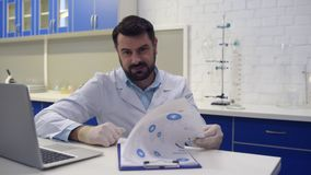 Científico de mirada amistoso que sonríe en cámara mientras que trabaja almacen de video