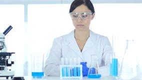Científico de Reseach que lleva los vidrios protectores que se sientan en laboratorio Foto de archivo