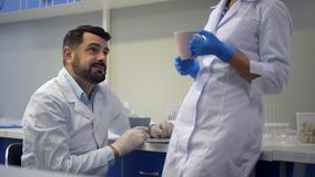 Científico de sexo femenino atento que trae la taza de té para el colega almacen de metraje de vídeo