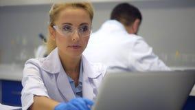 Científico de sexo femenino elegante en gafas de seguridad que mecanografía en el ordenador almacen de video
