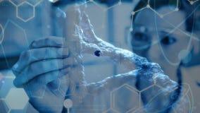 Científico de sexo femenino de la composición de la ciencia que sostiene una muestra de microorganismo combinada con a almacen de video