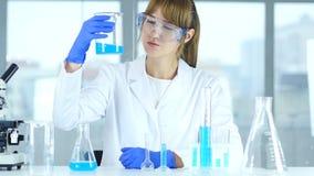 Científico de sexo femenino de la investigación que mira la solución en cubilete en el laboratorio, reacti almacen de video