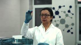 Científico de sexo femenino mayor que trabaja en un microscopio en su laboratorio almacen de video