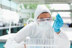 Científico de sexo femenino protegido que sostiene un tubo de prueba fotografía de archivo libre de regalías