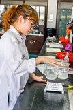 Científico de sexo femenino que examina la solución hervida de la sustancia química del cubilete Foto de archivo libre de regalías