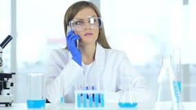 Científico de sexo femenino que habla en el teléfono en laboratorio almacen de video
