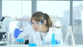 Científico de sexo femenino que mira la reacción que sucede en frasco en laboratorio almacen de video