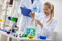 Científico de sexo femenino sonriente que usa el líquido de la química para la investigación imagen de archivo