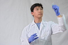 Científico de sexo masculino asiático que mira el pequeño tubo de ensayo Imagenes de archivo