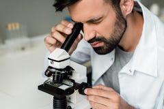 Científico de sexo masculino en la capa blanca que trabaja con el microscopio en laboratorio químico foto de archivo libre de regalías