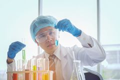Científico de sexo masculino joven en el técnico de laboratorio que hace la investigación médica en el MES fotos de archivo
