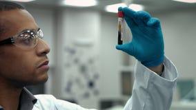 Científico de sexo masculino joven que examina un tubo de ensayo llenado de la sangre que trabaja en el laboratorio metrajes
