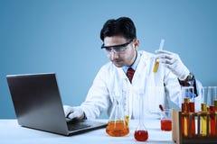 Científico de sexo masculino que hace la biotecnología fotografía de archivo libre de regalías
