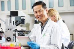 Científico de sexo masculino que usa el ordenador de la tablilla en laboratorio Imágenes de archivo libres de regalías