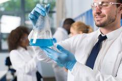 Científico de sexo masculino Working With Flask en el laboratorio que hace la investigación sobre la raza Team Of Lab Workers de  Foto de archivo