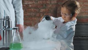 Científico del niño que vierte el nitrógeno líquido de la botella de termo de acero en cubilete almacen de metraje de vídeo