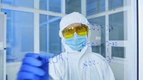Científico en el traje protector que dibuja fórmulas químicas sobre el vidrio almacen de video