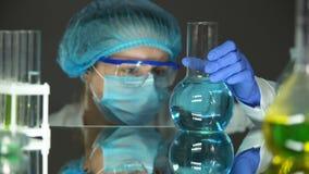 Científico en el uniforme protector que mira el líquido azul en el frasco, análisis de agua metrajes