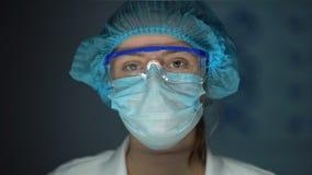 Científico en el uniforme protector que mira a la cámara, doctor cansado después de la cirugía almacen de video
