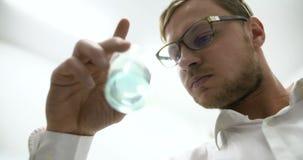 Científico en líquido de examen del laboratorio en el cubilete de cristal almacen de video