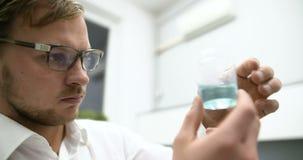 Científico en líquido de examen del laboratorio en el cubilete de cristal almacen de metraje de vídeo